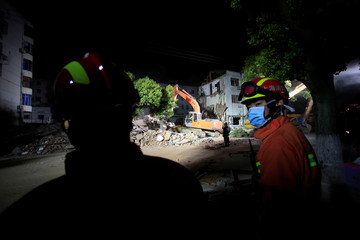 Rescue workers search at the site after a three-storey residential building collapsed in Shanghai