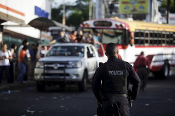 A policeman guards a bus stop during the fourth day of a suspension of public transport services in San Salvador