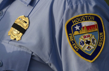 A fireman's badge is covered with black ribbon during a memorial service for four Houston firefighters in Houston, Texas