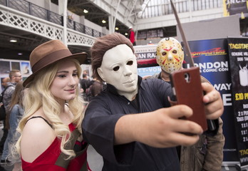 Cosplay fans dressed as horror film characters Freddy Krueger, Mike Myers and Jason Vorhees take a selfie photograph at the London Film and Comic-Con in London
