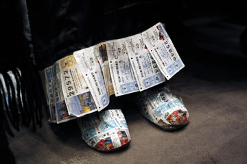 """A woman wearing shoes and dress adorned with old lottery tickets attend the draw for Spain's Christmas Lottery """"El Gordo"""" in Madrid"""