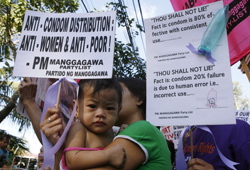 Protesters display placards and an inflated condom to promote the use of condoms in Manila