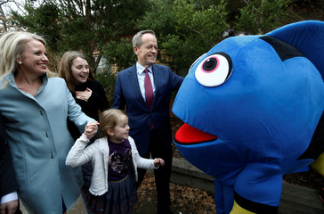 Australian Labor Party opposition leader Bill Shorten meets a protester dressed as animation film character Dory as he arrives to cast his ballot with his wife and children in Melbourne