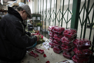 A man packages rose petals from Ecuador at Liberty Wholesale in the flower market in preparation for Valentine's Day in Los Angeles