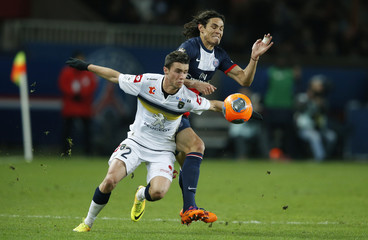 Paris St Germain's Edinson Cavani challenges FC Sochaux's Sebastien Corchia during their French Ligue 1 soccer match at the Parc des Princes Stadium in Paris