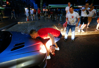 A Poland fan kisses a bonnet of a French car in St. Etienne  - EURO 2016