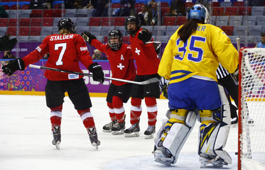 Switzerland's Lutz celebrates her goal against Sweden's goalie Wallner with teammates Benz and Stalder during the third period of their women's ice hockey bronze medal game at the Sochi 2014 Winter Olympic Games