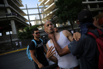 Opposition supporters grab a man they accused of being an infiltrate while rallying against President Nicolas Maduro in Caracas