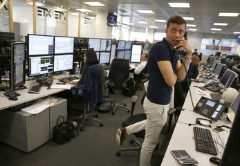 A trader at ETX Trading speaks on the telephone at their offices in London