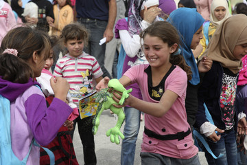 A Syrian refugee girl plays with a second-hand toy at the Al Zaatri refugee camp in Mafraq