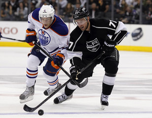 Los Angeles Kings center Jeff Carter takes the puck away from Edmonton Oilers left wing Taylor Hall during the third period of their NHL hockey game in Los Angeles