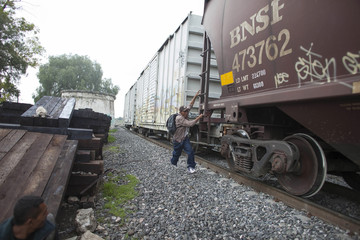 A migrant demonstrates to his friend how to catch a moving train in Atitalaquia, outskirts of Mexico City