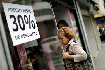 A woman looks at store's showcase displaying a discount sign in Caracas