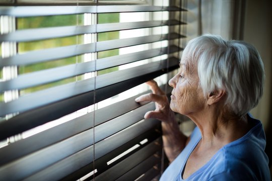 Senior woman looking out from window blind