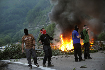 Miners on strike stand near barricades of burning tyres and tree trunks on the AP-66 motorway, between Asturias and Leon, in Pola de Lena