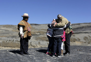 Bud Lane and his family have a hug as an Aymara man looks on during a ceremony at La Cumbre, on the outskirts of La Paz