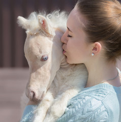 Wall Mural - Young cute woman kissing miniature foal. Close up photo.