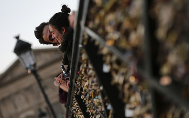 A couple embraces as they enjoy sunset on the Pont des Arts with its fence covered with padlocks clipped by lovers over the River Seine in Paris
