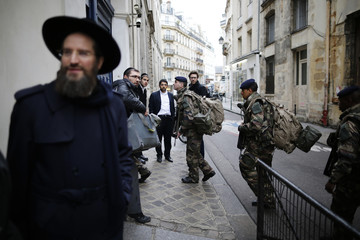 "French soldiers arrive to secure the access to a Jewish institution in Paris as part of the highest level of ""Vigipirate"" security plan after last week's attacks by Islamist militants"