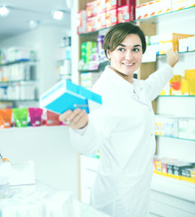 Professional pharmacist girl is showing right drug