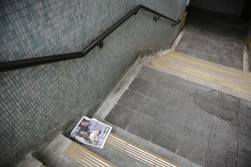 A discarded newspaper, featuring a picture of the newborn baby of Catherine, Duchess of Cambridge and Britain's Prince William, lies in a pedestrian tunnel in London