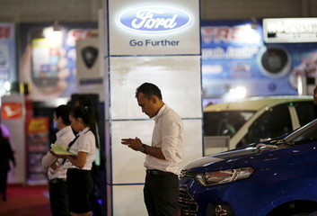 A salesperson waits at the Ford display at a car exhibition inside the Jakarta Fair in Jakarta, Indonesia