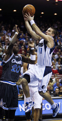 Dallas Mavericks guard Barea goes to the basket as he is defended by Orlando Magic forward Pietrus during first half NBA basketball action in Orlando