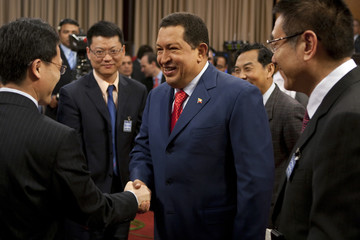 Venezuela's President Chavez shakes hands with Haier's Vice-President Liang during a agreement-signing ceremony in Caracas