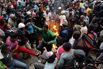 Protestors burn cardboard and refuse as they demonstrate against a lack of housing and other services outside provincial government buildings in central Cape Town