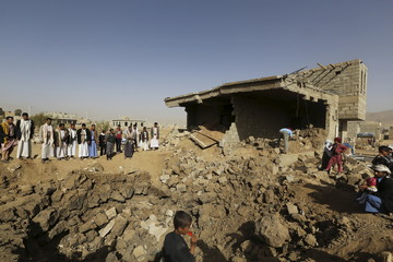 People gather at the site of an air strike in Amran province