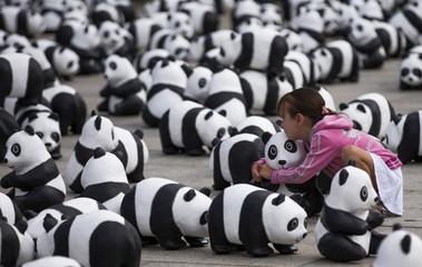 Girl embraces panda bear sculpture in Berlin