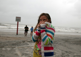 Rhiannon Shaw, 9, tries to stay warm while checking out the beach with friends as Hurricane Irene passes through Wrightsville Beach, N.C.