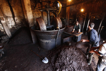 Workers prepare to extract oil from olive paste at a traditional olive oil processing factory in the eastern village of Al Kalaa, near Bejaia