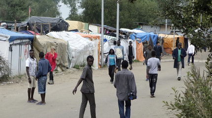 """Migrants walk in the northern area of the camp called the """"Jungle"""" in Calais, France"""