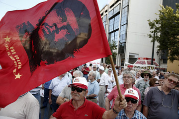 A pensioner raises a flag depicting Che Guevara during an anti-austerity rally in Athens