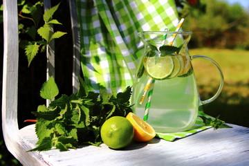 газированный лимонад в кувшине на стуле в саду