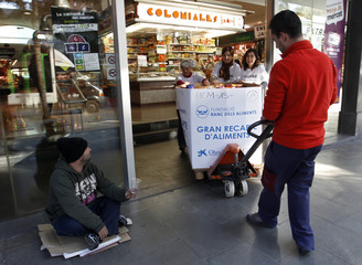 Volunteers pull a trolley with non-perishable food collected at a market during a charity campaign in Barcelona