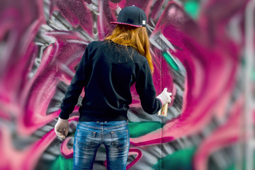 Young urban girl draws graffiti, contemporary iconic culture of street youth. Modern iconic urban culture street. Concept modern design. Street art graffiti. selective focus