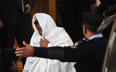Police officers escort a man, who covers himself with a cloth, as he leaves after appearing before the Supreme Court in Islamabad