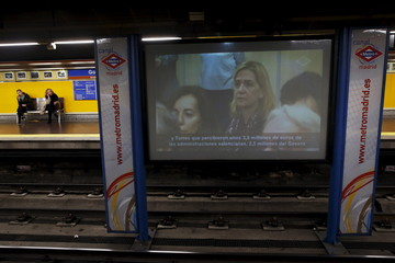 A TV screen shows footage of Spain's Princess Cristina sitting in court facing charges of tax fraud, as a long-running investigation into the business affairs of her husband Inaki Urdangarin goes to trial, at a metro station in Madrid