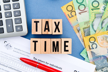 Tax Time - Australia - wooden letters with tax form, money and calculator