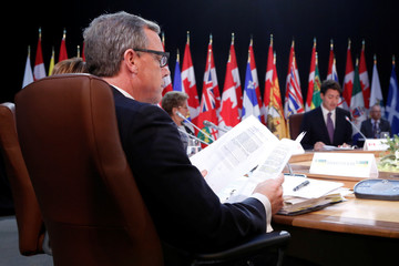 Saskatchewan Premier Brad Wall looks at papers as Canada's Prime Minister Justin Trudeau speaks during the First Ministers' meeting in Ottawa