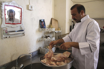 A Free Syrian Army cook prepares chicken for fellow fighters in a Free Syrian Army kitchen located near the frontline in the al-Khalidiya neighborhood of Aleppo