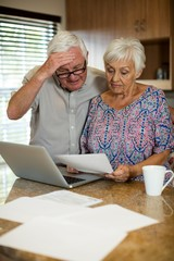 Senior couple calculating their invoices with laptop