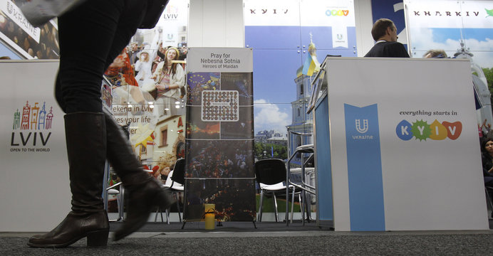 A lit candle is placed next to a booth representing Ukraine during the International Tourism fair (ITB) in Berlin