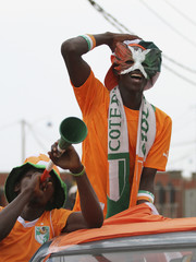 Ivory Coast fans, wearing shirts in the colours of the Ivory Coast national flag, cheer in a street in Malabo