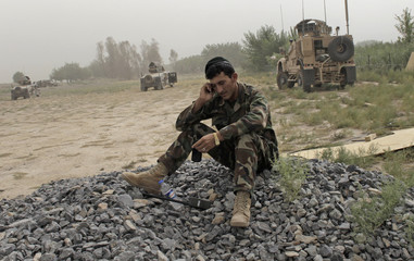 An Afghan Army soldier talks on phone after his unit arrived at Combat Outpost Nolen in the Arghandab Valley