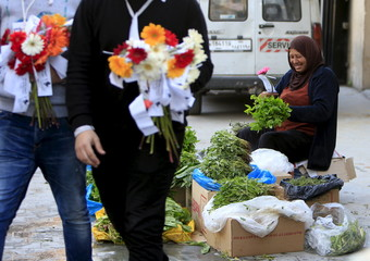 A herb vendor smiles after receiving a flower from leftist politically affiliated youths during International Women's Day at the port city of Sidon, southern Lebanon