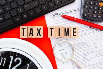 Tax Time - USA - wooden letters with 1040 Tax Form, magnifying glass, clock, keyboard and calculator