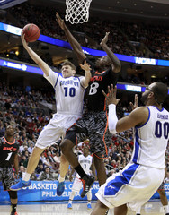 Creighton Bluejays Grant Gibbs (L) shoots under pressure from the Cincinnati Bearcats Cheikh Mbodj during the second half of their second round NCAA tournament game in Philadelphia
